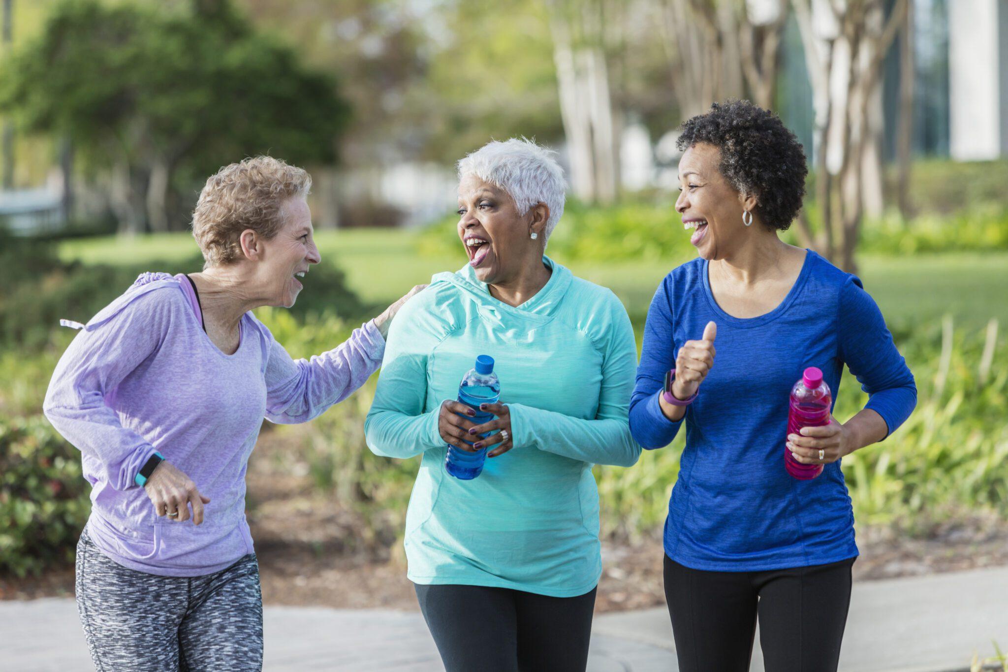 Three Mature Women Exercising In Park, Walking, Talking