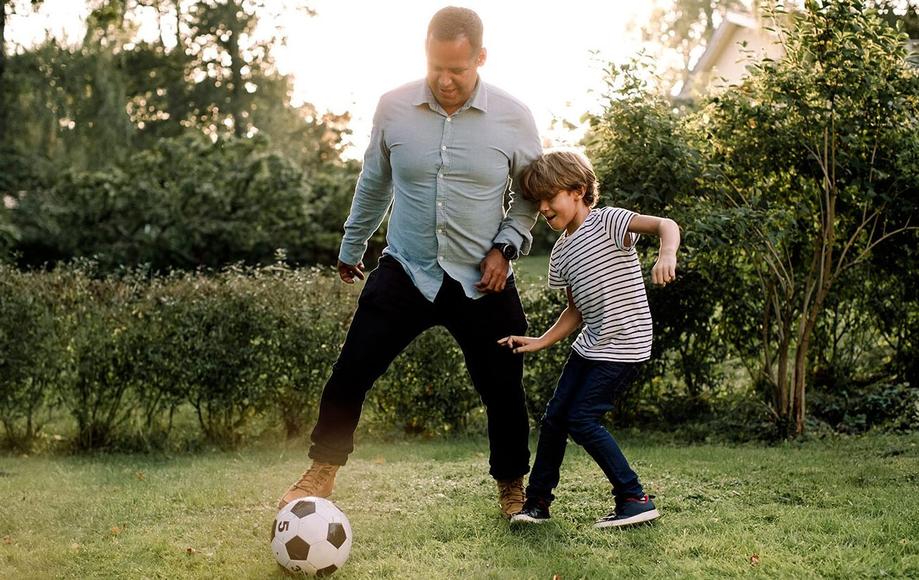 Full Length Of Father And Son Playing Soccer In Backyard During Weekend Activities