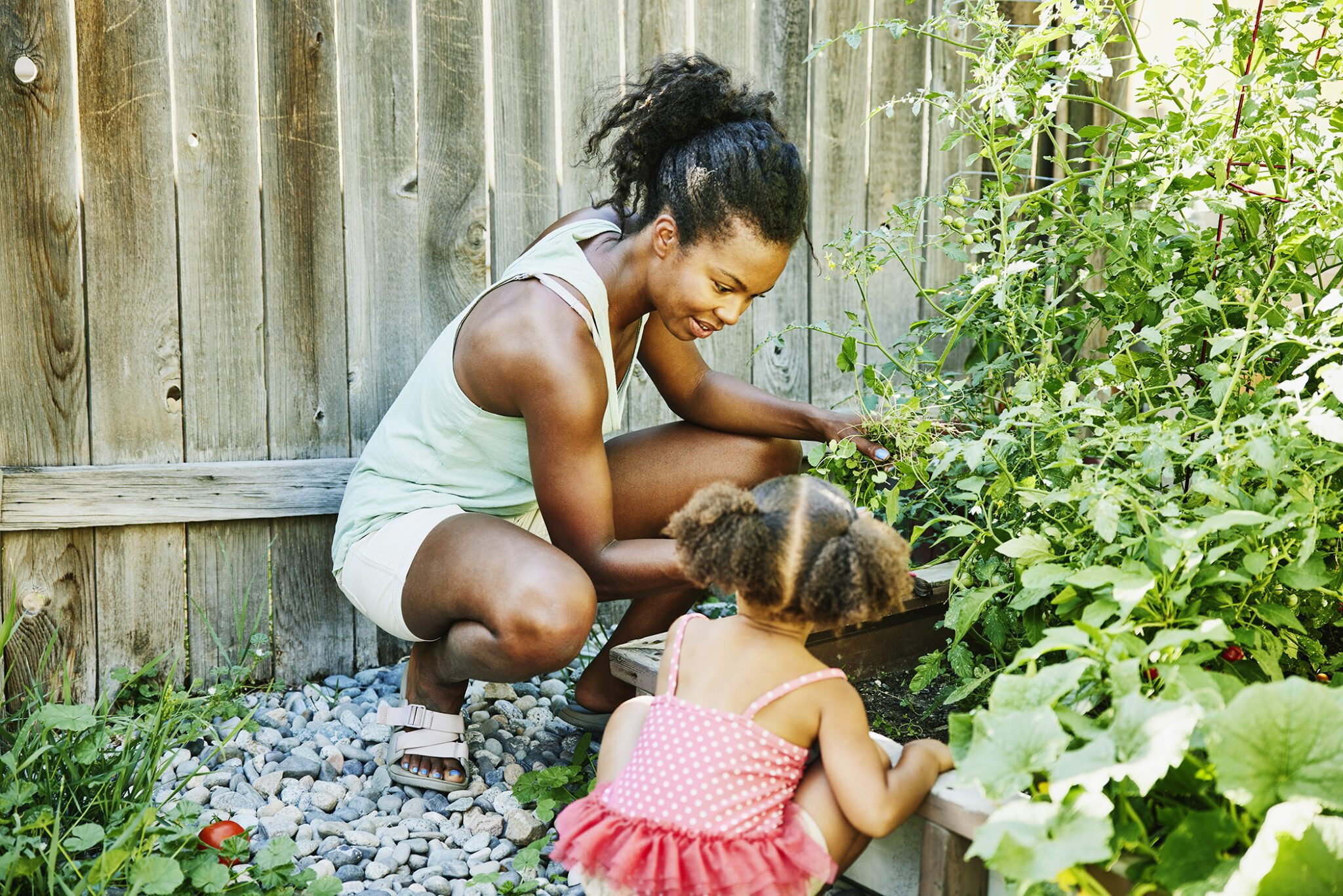 Smiling Mother And Young Daughter Tending To Plant Beds In Backyard Garden